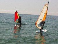 Dos personas en windsurf y una en paddle surf