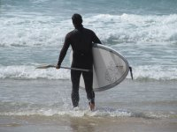 Entering the water with the board and paddle