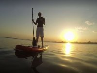 Paddle surf to watch the sun set