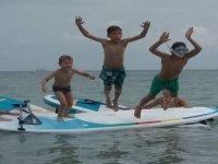Pequeños saltando de las tablas de paddle surf