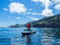 De pie en moto de agua junto a los acantilados