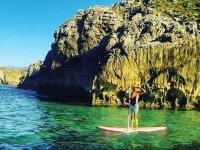Walking along the cliffs in sup board