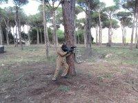 Disparando apoyado en el arbol