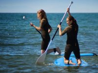 Girls kneeling on sup boards