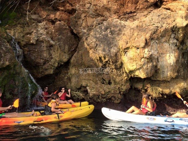 Kayaks bordeando las rocas de la costa