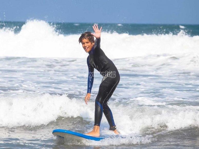 Alumno de surf de pie sobre la tabla