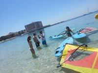 Velas de windsurf tumbadas en el agua