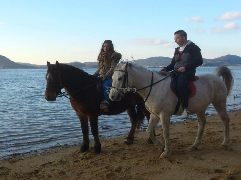 Pareja a caballo en la playa