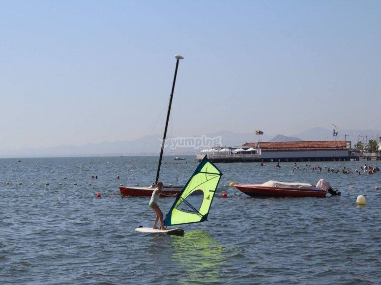 Alumna de windsurf levantando la tabla