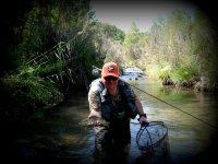 Dentro del río con el pez en la mano