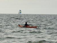 Kayak y velero al fondo