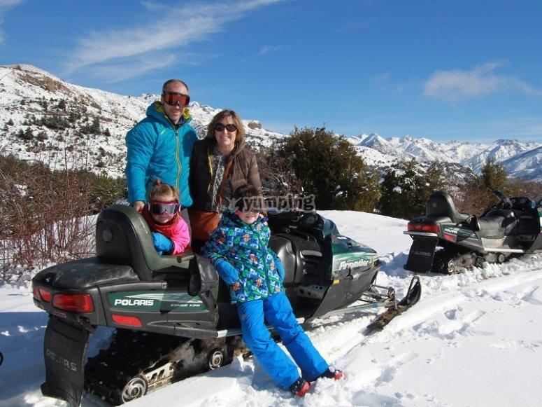 Familia junto a la moto de nieve