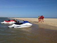 Chicas a la orilla del mar con las motos de agua