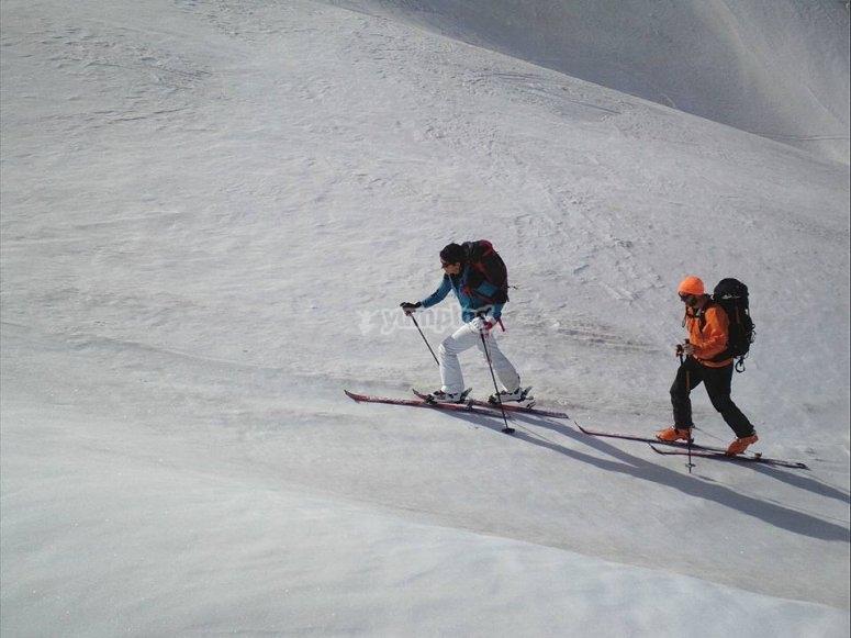 Ascenso de esquiadores por pista