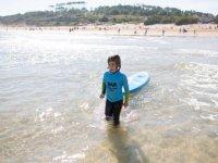 Alumno llevando la tabla al agua en Cantabria
