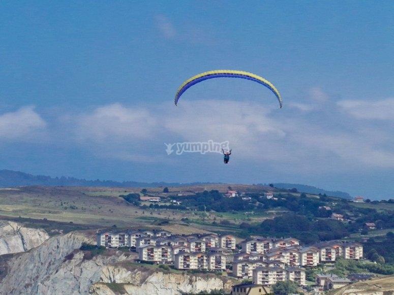 Parapente volando sobre urbanizacion