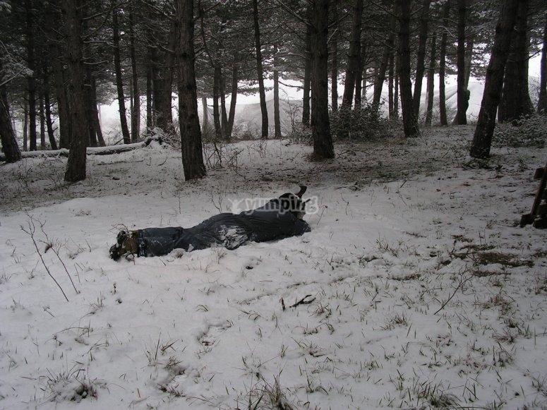 Jugador de paintball tumbado sobre la nieve
