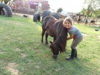 Peque sorride accanto al pony