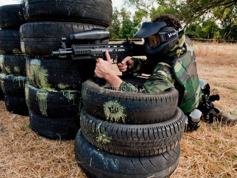 Apoyado en los neumaticos para disparar