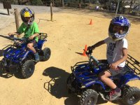 Niños equipados con casco y quad