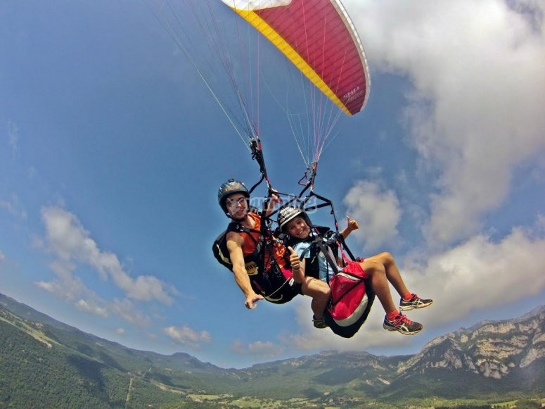 Paragliding pilot and a young passenger