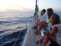 Seduto per vedere come il sole tramonta dalla barca