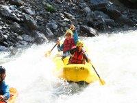 Pareja en canoa por aguas bravas