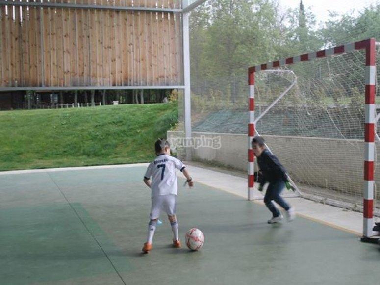 Dos ninos jugando al futbol en un polideportivo
