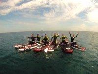 开心的团体男孩做桨冲浪