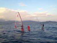 dos chicos de windsurf haciendo el giro