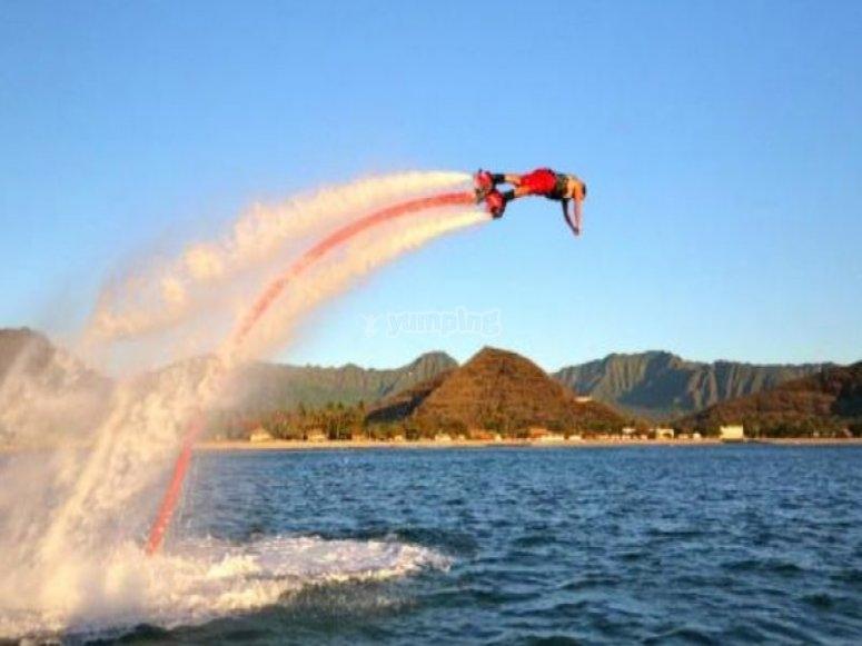 Hombre a punto de sumergirse en el agua mientras practica flyboard
