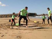 Clase práctica de surf en la arena.