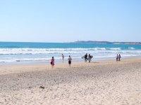 Surfistas caminando por la playa de Conil