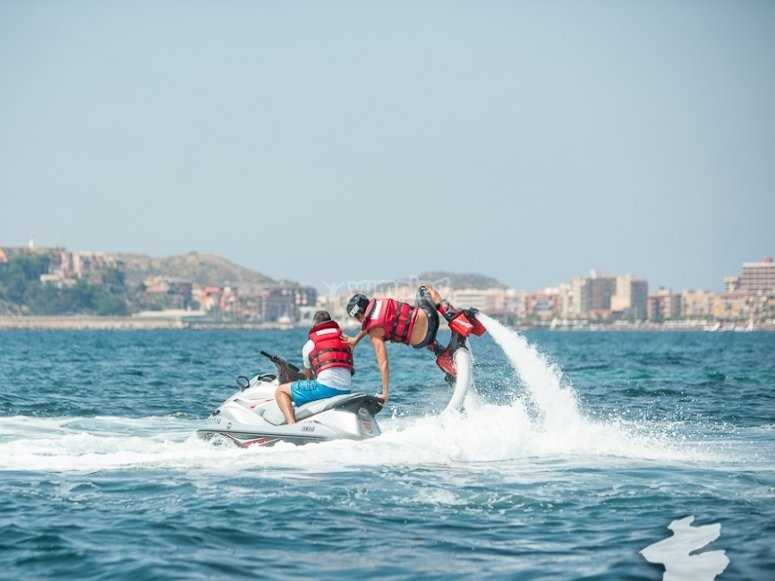 Holding to the instructor who is on the jet ski