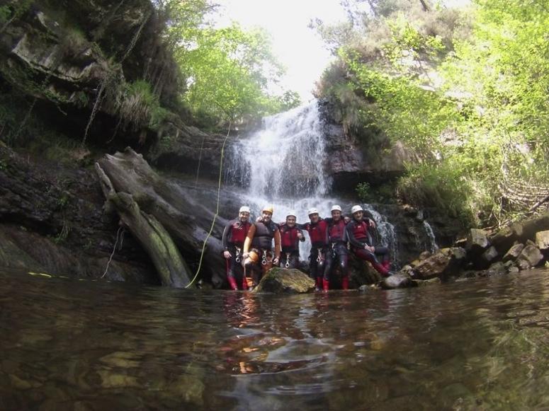 Amigos bajo la cascada del barranco
