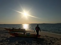 Kayaks on the shore at sunset