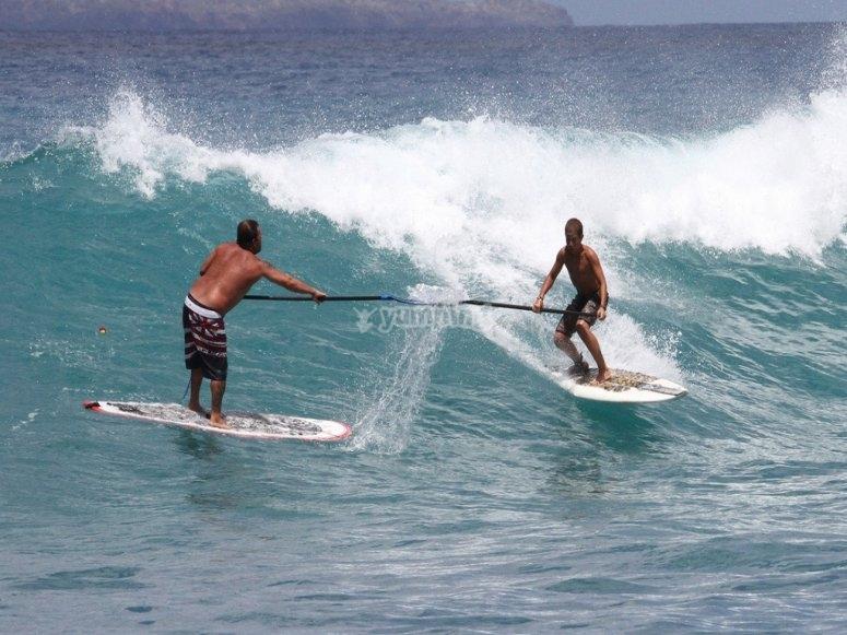 Monitor y alumno de paddle surf
