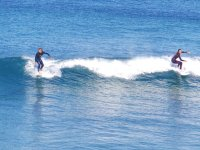 Surfers in various parts of the wave