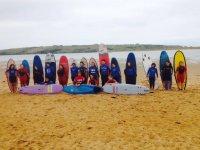Alumnos de pie con sus tablas de surf