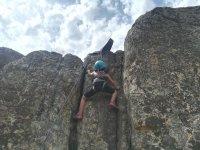 Joven escalando la pared rocosa