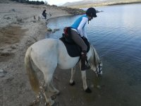 Sobre el caballo mientras este bebe agua