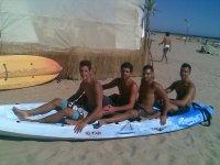 chicos sobre una tabla de surf en la playa