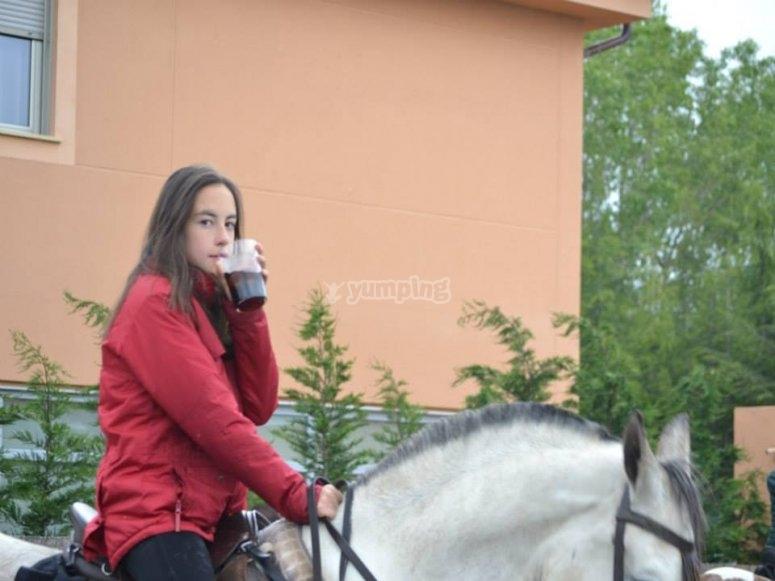Bebiendo un refresco mientras pasea a caballo
