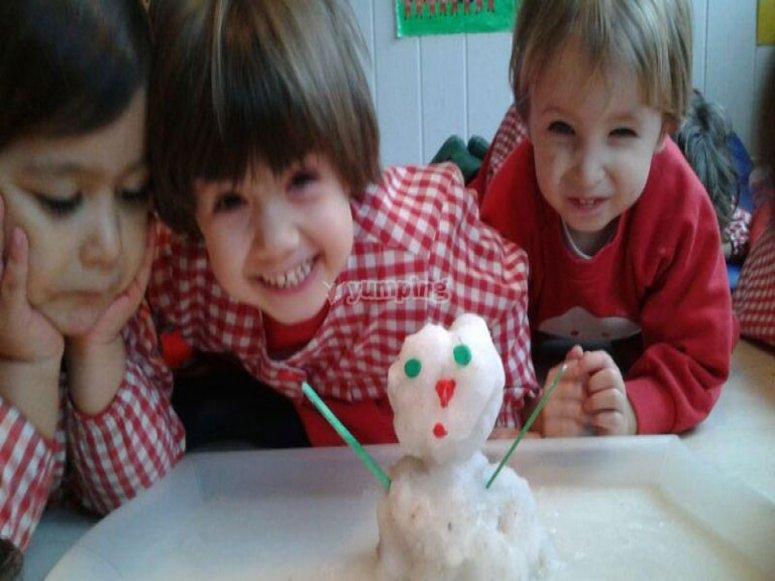 ninios haciendo un muneco de nieve