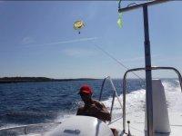 Patron con el parasailing sobre el barco