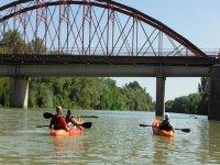 Kayak bajo el puente en el rio