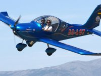 A blue ultralight flying