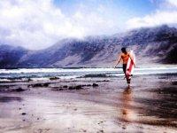 Caminando por la playa con la tabla de surf