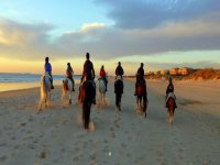 Paseo a caballo en la playa al atardecer