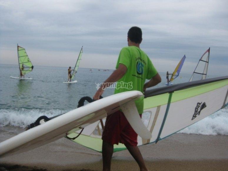Llevando la tabla y la vela de windsurf